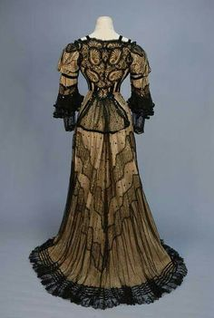 Trained black lace evening how with sequins.  1905