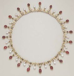 AN ANTIQUE ENAMEL, PEARL AND GARNET NECKLACE, BY CARLO GIULIANO   Designed as a series of scrolled black and white enamel links, suspending a fringe of cabochon garnet collets, to the smaller black and white enamel spacers, each suspending a baroque pearl drop, mounted in gold, circa 1870, 15 ins., in a Harvey & Gore burgundy leather retailer's case  Signed CG for Carlo Giuliano