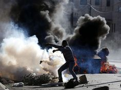 A Palestinian protester throws a tear gas canister during clashes with Israeli troops in the outskirts of the West Bank city of Bethlehem.   Abed Al Hashlamoun, European Pressphoto Agency