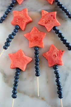 Fruit kebabs on a white marble board, called fruit sparklers, with blueberries and a watermelon star secured on a wood skewer.