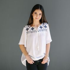 Embroidered loose fitting top with tie front closure and short sleeves  Approximate bust measurement:  Small – 44″            Medium – 46″            Large – 48″  Approximate length:  Small – 26″  Medium – 27″  Large – 28″  Fabric content:  Cotton, Polyester