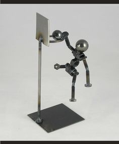 Statue made of nuts, bolts, a steel ball and other recycled metal depicting a player stuffing the basketball thru the hoop