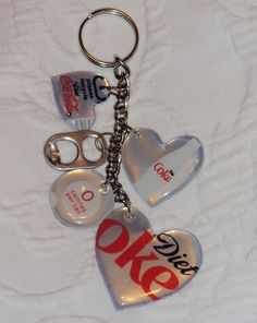 Fun themed key chain fob. Cut the logos out of pop cans. Glue two together with xx. Punch a hole, then cover in Mod Podge Dimensional Magic. Let dry between coats and keep repunching the hole. Do three coats. Add jump rings and attach various charms along with the pop logos.