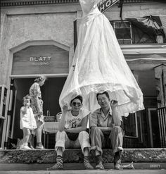 "July 1940. ""Street scene at the fiesta in Santa Fe, New Mexico."" Our third look at the festive goings-on here, and we'll let someone else explain the skirt-brella. Photo by Russell Lee for the Farm Security Administration."