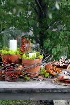 Cute outdoor table idea - Different size clay pots, moss, glass hurricanes, candles, branches, fall foliage