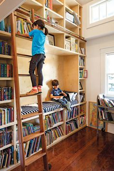 Home library with ladder and a reading nook. Looks like Heaven to me.I'd just need a more adult-friendly reading nook and a room at home to build it all in!