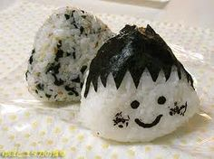 Cute rice ball.  Wrapped with seaweed and sesame seeds.