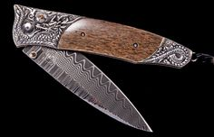 The Gentac 'Dracha', by William Henry, features a beautiful frame in hand-carved sterling silver, inlaid with 10,000 year-old woolly mammoth bone. The blade is Wave damascus with an extra strong core in ZDP-189; the one-hand button lock and the thumb stud are set with smokey quartz.