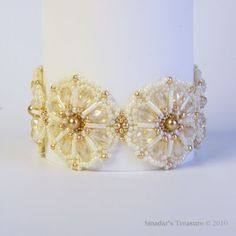 This textured daisies bracelet is beadwoven with transparent Czech glass faceted drop beads in golden shadow; opaque cream bugle beads, opaque