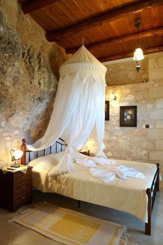 Cave bedroom with stone walls and overhead canopy in Greece