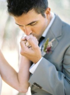 Groom kissing bride's hand, 45 degrees to camera