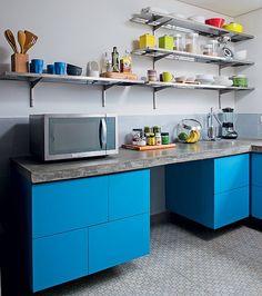 O desenho da cozinha deste apartamento foi pensado para lembrar as antigas do tipo industrial. Por isso, a equipe do arquiteto Vitor Penha criou as prateleiras de aço inox escovado. O balcão é de concreto