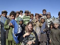 Rachel Washburn, 1st Lieutenant, U.S. Army, intelligence officer in her first deployment to Afghanistan in 2011-12, poses for a photo with a group of children.
