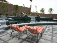 Bright orange and red striped lounge chairs pop against the curved pool finished with gray concrete and mosaic tile.
