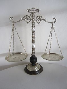 A vintage silver toned justice scale. It was made as a decorative piece but does move when weight is applied. The base is wood and the chains holding the trays are brass. Perfect for a shelf or lawyers office.