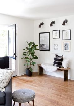 rustic modern entryway with simple gallery wall, wood bench, plants, and black and white accents