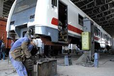 Dos mecánicos reparan una locomotora