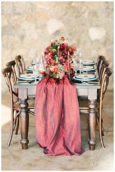Wedding reception tabletop with centerpiece florals in brilliant jewel tones and a crimson silk runner. Planning by Cheers Darling Events with florals by Holly Heider Chapple Flowers of Hope Flower Farm. Photographed by Elizabeth Fogarty on location at Stone Tower Winery in Virginia.
