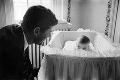 Senator John F. Kennedy plays peek-a-boo with daughter Caroline in 1958...