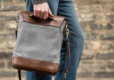 man holding leather field bag