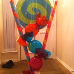 "5' Lollipops! I made these (15 of them) for my daughter's Sweet Sweet 16 party! It's made with 1"" foam and PVC. (You can cut 8-2' circles out if one 4x8 sheet of this from Home Depot) The candies are just white foam plates stapled together and wrapped in colored cellophane. The candy sticks are pool noodles and colored duct tape wrapped in clear cellophane."