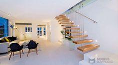 Białe wnętrze przełamane drewnianymi schodami | oświetlenie Delta Light