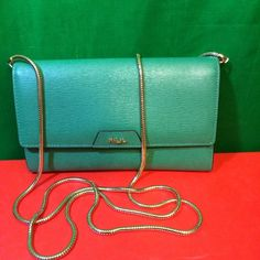 "Ralph Lauren Tate Mini Chain Clutch Saffiano Green Ralph Lauren Tate Mini Chain Cross-body Saffiano Green Fern Cocoa Leather  Flap closure with a concealed magnetic closure. Golden cross-body chain strap. Exterior slip pocket at the back. Interior features a slip pocket at the front wall, a zip change pocket at the center printed with a signature ""Lauren Ralph Lauren"" logo, two compartments with room for a checkbook, six card slots and a full currency pocket. Embossed metallic ""RLL"" accents…"