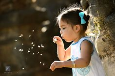 Little girl blowing dandelions