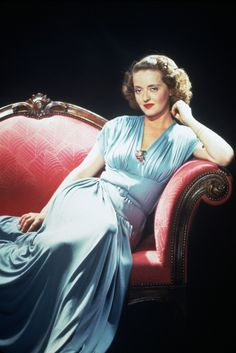 1943. Bette Davis works a blue gown in this seductive shot. Note her soft draped dress across her legs, only her arms are exposed in this dress.