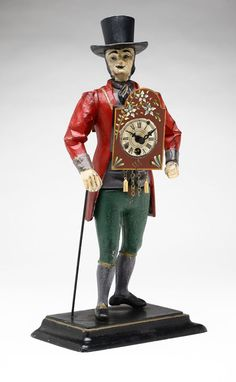 A Continental painted tole painted metal figural peddler clock. 20th century, possibly Austrian or German, the figure with top hat, coat and britches, supporting clock face and movement to center, with faux face to reverse, on a stepped rectangular integral base.