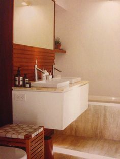 Custom teak vanity, travertine marble countertop, Axor sink faucets by Starck for Hansgrohe