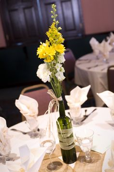 Country wedding-wine bottle wrapped in ribbon with daisies and gypsum, and babies breath at varying heights. Tied with raffia, burlap table runners.