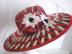 Now thats a Derby hat! In fact, this hat was selected to be on display in the Kentucky Derby Museum for a year. Classic wide brim with an intricate lattice pattern woven on top of the brim. Two gorgeous feather flowers and lots of wispy feathers make it Derby style that will be the envy of everyone who see it! A Large, sumptuous silk band and stylized flowers complete the look. The straw hat is black with red and white woven accents. A windowpane sinamay overlay tops the crown of the hat…