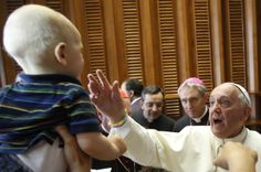 Pope Francis blesses a baby during an audience in the Paul VI hall at the Vatican, Saturday, May 31, 2014. The pontiff met with children from poor neighborhoods in Naples and Rome at risk of leaving school.