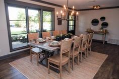 The newly configured dining space features a contemporary chandelier in brushed bronze finish and a dining table custom made by furniture artisan Clint Harp.