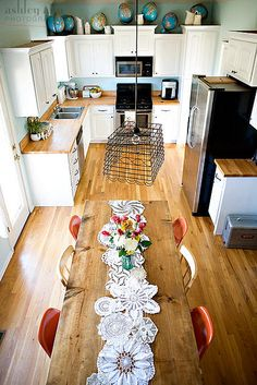 love this simple kitchen's fine details - globes, doily table runner, wire basket light