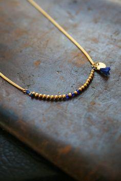 Un collier tout en délicatesse, doré à l'or fin, orné de perles or sur un fils de soie, rehaussé de perles indigo ou rouge et de pampilles (un sequin et un pompon accordé au tube coloré). Merci...: