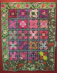 An asymmetrical quilt, with a freely designed bottom border. Tiny pieces with cool & pastel colors. Divine.