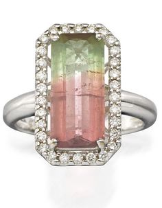 *TOURMALINE AND DIAMOND RING  Of cluster design centring a rectangular parti-colour tourmaline weighing approximately 4.00 carats within a brilliant-cut diamond surround, the diamonds together weighing approximately 0.30 carats, mounted in 18ct white gold,.
