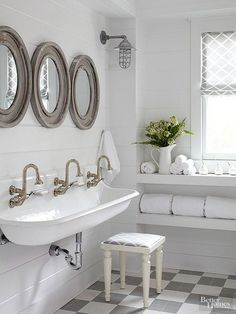 Beautiful white farmhouse bathroom with planked walls, wood mirrrors and large farmhouse sink.