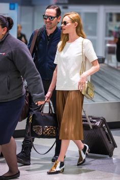 Kate Bosworth looking sleek in a simple blouse and pleated skirt at the airport // #Fashion #Style