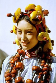 Beautiful Khampa lady resplendent in traditional headdress and ceremonial costume adorned with chunks of amber, Tibet: To the Khampa people these ornaments have the utmost significance because they are physical remnants of their ancestors' success.