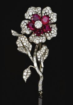 RUBY AND DIAMOND BROOCH, VAN CLEEF & ARPELS,  1952.  Designed as a flower, the petals set with oval rubies and brilliant-cut diamonds, the stem set with baguette stones, to brilliant-cut diamond set leaves, mounted in platinum, signed Van Cleef & Arpels and numbered, French assay and maker's marks, case.