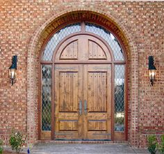 "DbyD-2037.  This Grand Country French Exterior Wood Entry is located here in Montgomery, AL.  It is handcrafted out of Knotty Alder.  This Unit consists of a pair of 36"" x 96"" Doors with a Solid Radius Transom and 16"" Wraparound Sidelites and transom.  The Leaded Seedy Diamond Glass adds Country Appeal.  A Rocky Mountain Lockset was chosen for this Unit.  Rocky Mountain Ornamental Strap Hinges and Clavos are applied to the exterior."