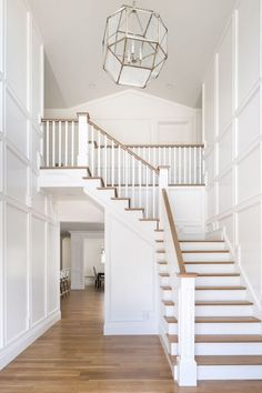 White entry and stairwell. Love the paneling details in foyer. Very elegant and serene design.