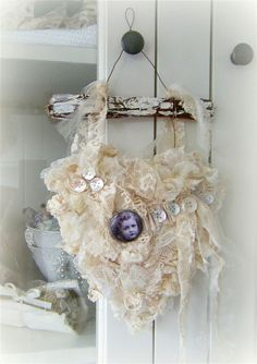 Beautiful use of old lace and buttons...maybe a brooch in the centre?