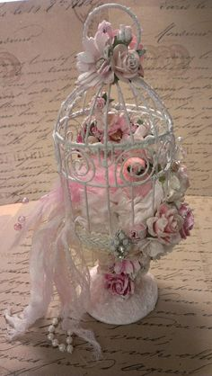 I created this adorable Shabby Chic bird cage on pedestal using a glass candle stick and a metal birdcage. It has an adorable pink bird with feathers inside the cage sitting on a shabby fluffy flower. It is all decked out with lots of chic pink and white paper Wild Orchid Craft flowers. It is trimmed in some sheer ruffled trim and a cream gimp. I added one of my own hand made stick pins and a pretty bling jewelry piece. I added some bead strand, seam binding and cheese cloth to extend the…