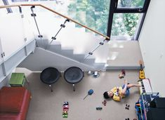 The kids play in the family room just beneath the stairs. Photo 23 of 204 in Best Kids Photos from Narrow Modernist Three-Story Home in Toronto. Browse inspirational photos of modern kids' rooms.