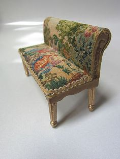 "Dollhouse Miniature Artisan Signed Upholstered Micro Petit Point measures approximately : 2 5/8""h (to the top of the bench) x 3 3/4""w, 1 1/2""h (to the top of the seat) Signed on the bottom: ""RACHEL B '12""  1/12"" Scale"