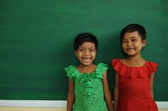 6-year-old Lae Lae Aung (in green) and 6-year-old May Tha Zin from Myanmar standing in front of a brand-new writing board. Their new school was built after Cyclone #Nargis ravaged southern parts of the country in 2008.